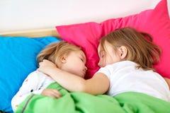 Niñas felices que duermen en cama en casa Foto de archivo