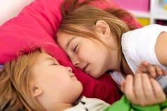 Niñas felices que duermen en cama en casa Imágenes de archivo libres de regalías