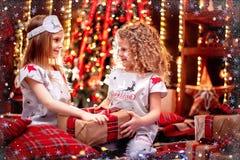 Niñas felices que llevan la caja de regalo abierta de los pijamas de la Navidad por a foto de archivo libre de regalías
