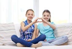 Niñas felices que muestran la muestra de la mano de la forma del corazón Fotos de archivo libres de regalías