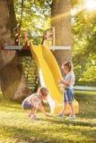 Niñas felices que ruedan abajo la colina en el patio Imagen de archivo libre de regalías