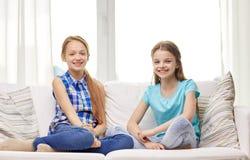 Niñas felices que se sientan en el sofá en casa Imagenes de archivo