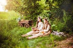 Niñas hermosas en un vestido blanco que presenta en la hierba Luz de la puesta del sol Imagen de archivo