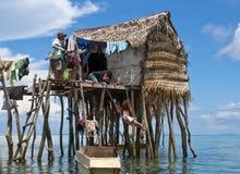2 niñas juegan en el oscilación debajo de la casa flotante Foto de archivo libre de regalías