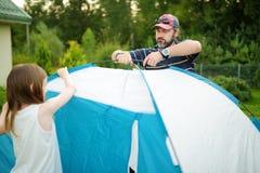 Niñas lindas que ayudan a su padre a poner una tienda en un sitio para acampar Forma de vida activa, fin de semana recreativo de  fotografía de archivo