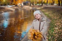 Niñas lindas que juegan en día hermoso del otoño Niños felices que se divierten en parque del otoño imagen de archivo
