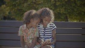 Niñas lindas que juegan a los juegos onlines en el teléfono móvil metrajes