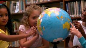 Niñas lindas que miran el globo en biblioteca almacen de video