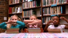 Niñas lindas que presentan con los libros de la biblioteca metrajes