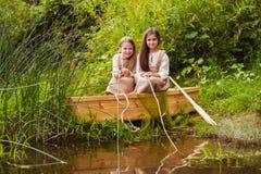 Niñas lindas que se divierten en un barco por un río Imagen de archivo