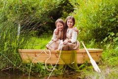 Niñas lindas que se divierten en un barco por un río Imagen de archivo libre de regalías