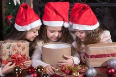 Niñas pequeñas divertidas que esperan sorpresa de la caja del presente del regalo Foto de archivo