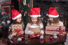 Niñas pequeñas divertidas que esperan sorpresa de la caja del presente del regalo Fotos de archivo libres de regalías