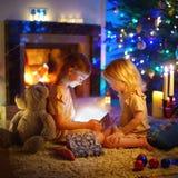 Niñas que abren un regalo mágico de la Navidad Imágenes de archivo libres de regalías