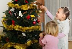 Niñas que adornan el árbol de navidad Fotos de archivo