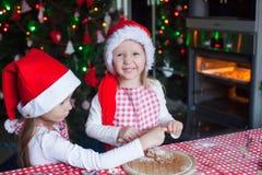 Niñas que cuecen las galletas del pan de jengibre en Papá Noel Fotos de archivo