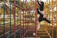 Niñas que disfrutan de subir en la estructura del metal en el patio fotografía de archivo libre de regalías