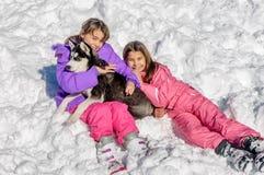 Niñas que juegan con el perro fornido en la nieve Imagenes de archivo