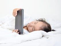Niñas que juegan en un dispositivo computacional de la tableta - poniendo en el th fotografía de archivo