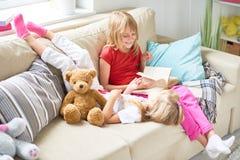 Niñas que leen cuentos de hadas en casa imagen de archivo