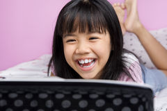 Niñas que ríen mientras que mira la computadora portátil Foto de archivo