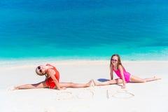 Niñas que se divierten en la playa tropical que juega junto en el agua poco profunda Fotos de archivo