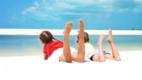 Niñas que se divierten en la playa tropical que miente junto en la costa Cámara lenta metrajes