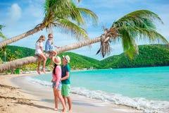 Niñas que se divierten que se sienta en la palmera Familia feliz que se relaja en la playa tropical con la arena y la turquesa bl Imagenes de archivo