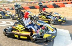 Niñas que se preparan para conducir el coche del kart en un ra del patio Foto de archivo libre de regalías