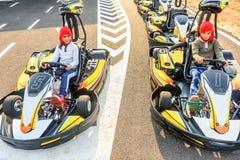 Niñas que se preparan para conducir el coche del kart en un ra del patio Imagen de archivo