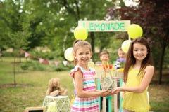 Niñas que sostienen el tarro con el dinero cerca de puesto de limonadas fotos de archivo libres de regalías