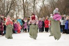 Niñas saco-que compiten con durante el carnaval de Maslenitsa del invierno en el Ru imágenes de archivo libres de regalías