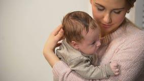 Niñera de sexo femenino atenta que detiene a poco bebé adorable y que habla con él metrajes