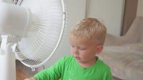 Niñez, concepto casero - niño pequeño lindo con el ventilador grande almacen de video
