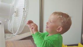 Niñez, concepto casero - niño pequeño lindo con el ventilador grande metrajes
