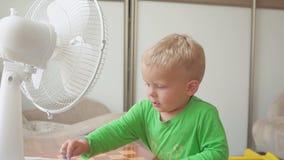 Niñez, concepto casero - niño pequeño lindo con el ventilador grande almacen de metraje de vídeo