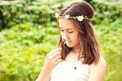Niñez despreocupada Muchacha con la manzanilla que huele de la mariposa Fotos de archivo libres de regalías