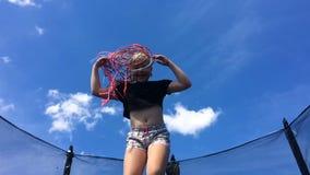 Niñez despreocupada, verano feliz muchacha hermosa con las coletas africanas que saltan en un trampolín - cámara lenta almacen de metraje de vídeo