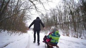 Niñez feliz en invierno, padre que camina con los niños en el trineo en bosque nevoso almacen de video