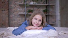 Niñez feliz, retrato de la niña hermosa con los ojos azules que mienten en la almohada en cama en sitio almacen de video