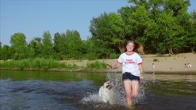 Niñez feliz y despreocupada El juego de niños con un perro, funcionamiento a lo largo de la arena, risa, juego en el río, lanza u almacen de metraje de vídeo