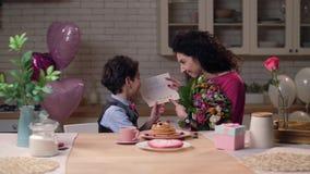 Niño árabe feliz que da a mamá la tarjeta de felicitación selfmade almacen de metraje de vídeo