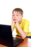 Niño aburrido con el ordenador portátil Imagenes de archivo