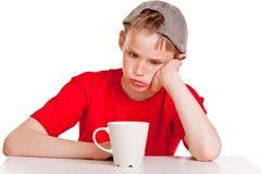 Niño aburrido con la taza blanca Fotos de archivo libres de regalías