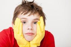 Niño aburrido en guantes con las manos en cara Imágenes de archivo libres de regalías