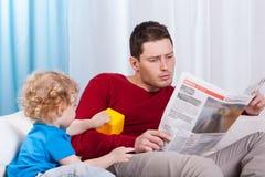 Niño aburrido que mira al padre Imagen de archivo libre de regalías