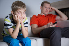 Niño aburrido que se sienta en el sofá Foto de archivo