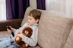 Niño aburrido que se sienta en el sofá y la TV de observación Fotos de archivo