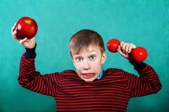 Niño activo divertido que sostiene el dumbbel rojo y la manzana grande Imagenes de archivo
