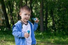 Niño activo que juega en el jardín en un día de verano soleado, hacia fuera actividades de las puertas para los niños Foto de archivo